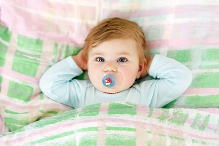 Adorable little baby girl after sleeping in bed. Calm peaceful child with a pacifier or dummy