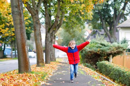 Happy little boy running on autumnal street after school.