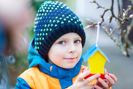 Little kid hanging bird house on tree for feeding in winter