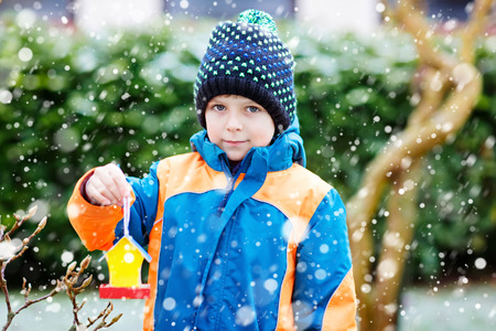 Little kid boy hanging bird house on tree for feeding in winter Stock Photo - 89007110