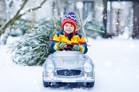 Funny little smiling kid boy driving toy car with Christmas tree. Stockfoto
