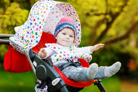 Cute little beautiful baby girl of 6 months sitting in the stylish pram or stroller and waiting for mom Stok Fotoğraf