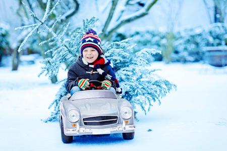 Pequeño muchacho sonriente divertido del muchacho que conduce el coche del juguete con el árbol de navidad. Foto de archivo