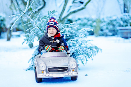 Funny little smiling kid boy driving toy car with Christmas tree. Foto de archivo
