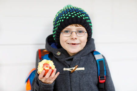 Little kid boy with eye glasses walking from the school and eating apple