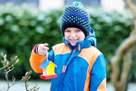 冬に授乳のための木の上に鳥の家をぶら下げ小さな子供の少年