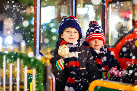 Two little kids boys on carousel at Christmas market