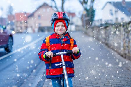 Cute little preschool kid boy riding on scooter riding to school. Zdjęcie Seryjne