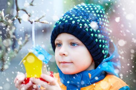 冬に食べるために木の上に鳥の家をぶら下げ小さな子供