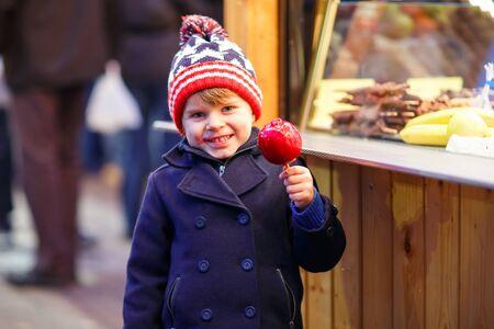 little kid boy eating sweet apple on Christmas market