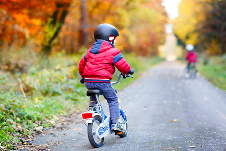 Two little kid boys cycling with bicycles in autumn forest park in colorful clothes