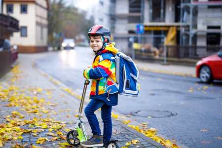 Cute little kid boy riding on scooter on way to school