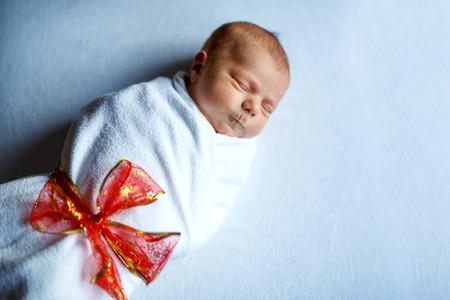 Una settimana di età bambino appena nato avvolto in una coperta bianca con fiocco rosso Archivio Fotografico - 90235023