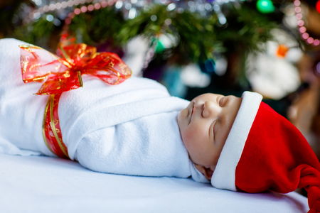 One week old newborn baby wrapped in blanket near Christmas tree Stock Photo