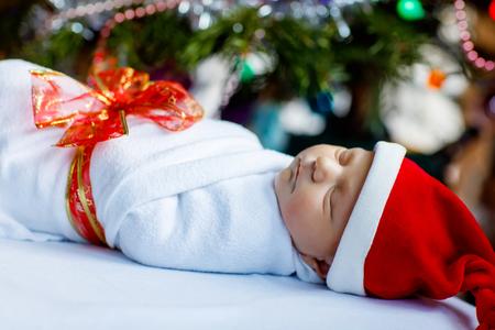 Un neonato di una settimana avvolto in una coperta vicino all'albero di Natale Archivio Fotografico - 90231735