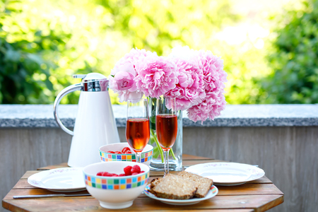 Breakfast table with bread, frest vegetables and berries, coffee and champagne served on balkony or hotel on summer morning