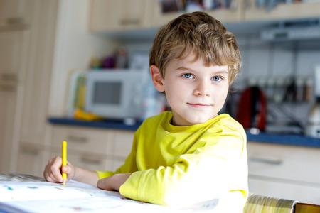 Happy school kid boy at home making homework