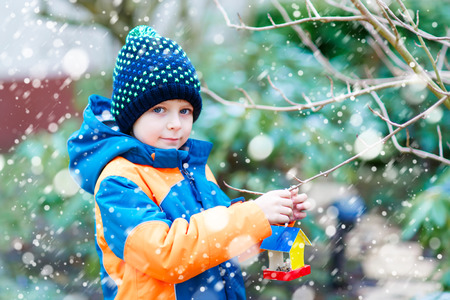 Little kid boy hanging bird house on tree for feeding in winter Stock Photo - 90371664