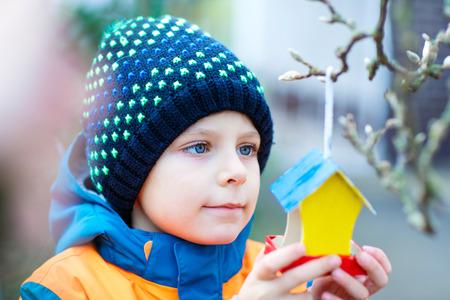 冬に餌を与えるための木の上に鳥の家をぶら下げる小さな子供 写真素材