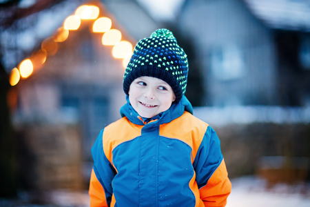 Happy kid boy having fun with snow in winter