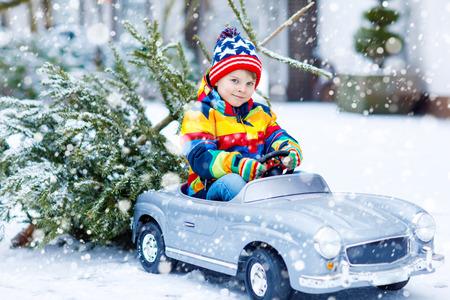 Pequeño muchacho sonriente divertido del muchacho que conduce el coche del juguete con el árbol de navidad. Foto de archivo - 91082050