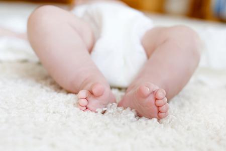 Füße und Beine des neugeborenen Babys mit Windel. Nettes kleines Mädchen oder Junge zwei Monate alte trockene und gesunde Körper- und Hautkonzept. Baby Kindergarten Standard-Bild