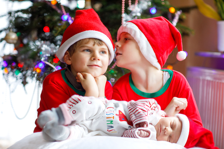 Newborn baby girl and two older brothers kid boys in Santa hat near Christmas tree