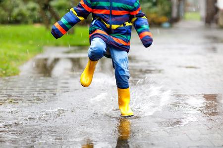 身に着けている黄色子供長靴のクローズ アップやみぞれ、雨や寒い日に雪の中にウォーキング 写真素材