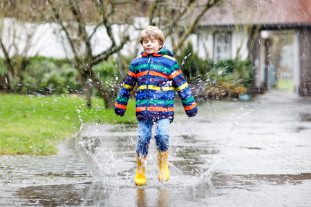 Little kid boy wearing yellow rain boots and walking during sleet, rain and snow on cold day