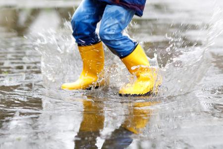 Nahaufnahme des Kindes gelbe Regenstiefel tragend und während des Schneeregens, des Regens und des Schnees am kalten Tag gehend Standard-Bild