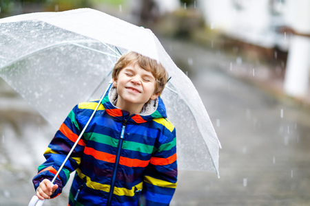 Little blond kid boy on way to school walking during sleet, rain and snow with an umbrella on cold day Foto de archivo
