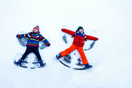 Two little siblings kid boys in colorful winter clothes making snow angel, laying down on snow. Banco de Imagens