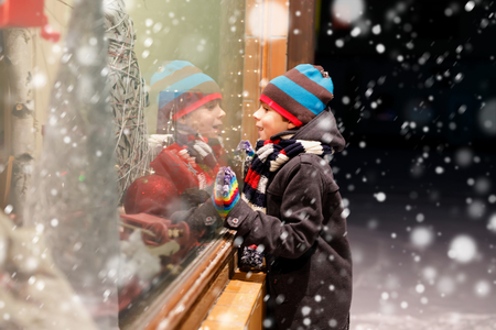 Funny happy child in fashion winter clothes making window shopping decorated with gifts, xmas tree