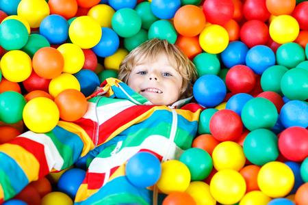 カラフルなプラスチックボールの遊び場で遊ぶ小さな男の子