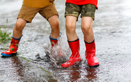 Two children wearing red rain boots jumping into a puddle. Stock Photo