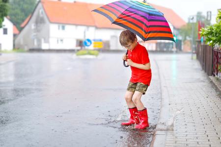 Jong geitjejongen die rode regenlaarzen dragen en met paraplu lopen