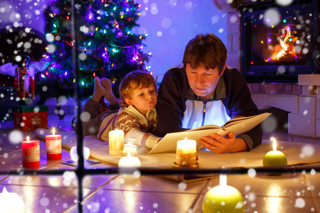 Father and cute little toddler boy reading book by chimney, candles and fireplace. Imagens