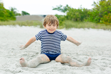 Little kid boy having fun on tropical beach