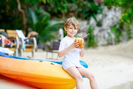 Little kid boy drinking coconut juice on tropical beach