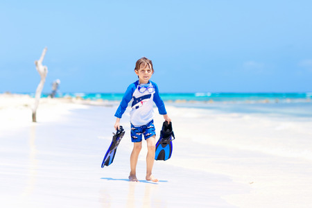 Adorable little blond kid boy having fun on tropical beach of Bora Bora. Excited child playing and surfing in sun protected swimsuit in ocean on vacations. White sand, Kid holding flippers for swimming