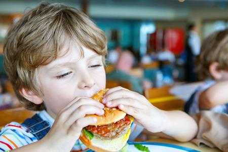 Cute healthy preschool kid boy eats hamburger sitting in school or nursery cafe. Happy child eating healthy organic and vegan food in restaurant. Childhood, health concept