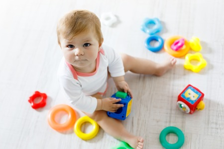 Adorable Baby Girl Playing With Educational Toys In Nursery Stock