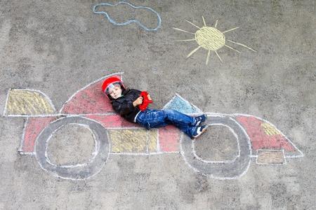 Entzückendes kleines Kind Junge Zeichnung mit bunten Kreiden Rennwagen Ziel auf Asphalt Standard-Bild - 93940091