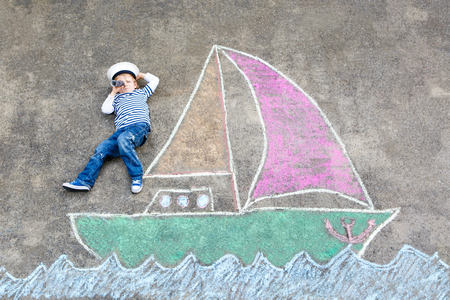 Little kid boy as pirate on ship or sailingboat picture painting with colorful chalks on asphalt. Archivio Fotografico