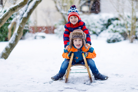 Two little kid boys having fun sleigh ride in winter