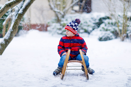 Little kid boy having fung with sleigh ride in winter