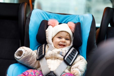 Adorable baby girl with blue eyes sitting in car seat. Toddler child in winter clothes going on family vacations and jorney