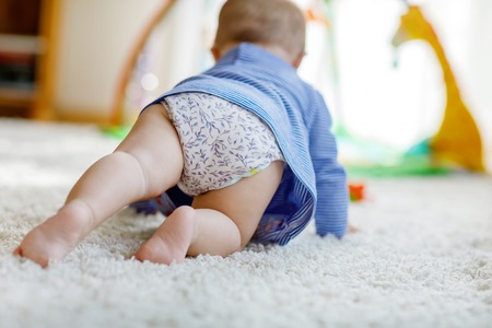 Little cute baby girl learning to crawl.