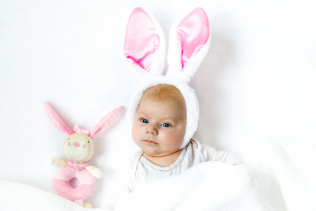 Adorable cute newborn baby girl in Easter bunny costume and ears.