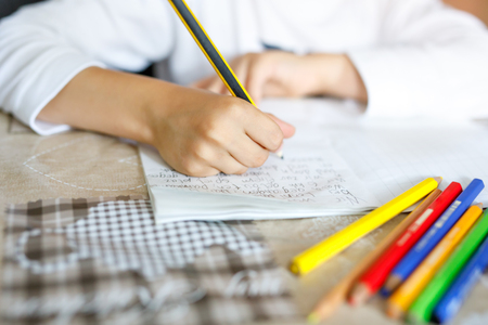 Child doing homework and writing story essay. Elementary or primary school class. Closeup of hands and colorful pencils Stock fotó - 93976351